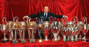 Una immagine di Silvio Berlusconi con i trofei conquistati dall'AC Milan nei 30 anni di gestione aziendale (foto tratta dal web)